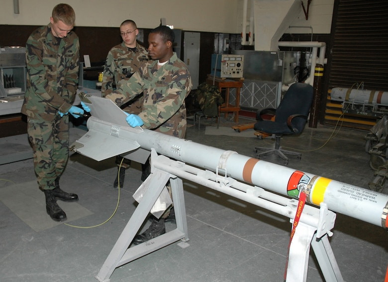 OSAN AIR BASE, Republic of Korea --  Airmen 1st Class Jesse Shaw and Theopolis Austin remove a fin from an AIM-9 missile while Airman 1st Class Cody Smith goes over the technical orders for the operation. (U.S. Air Force photo by Staff Sgt. Benjamin Rojek)