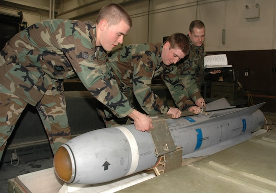 "OSAN AIR BASE, Republic of Korea --  Airmen 1st Class Mark Stoia and Justin Simmons pull a Training Guided Missile-65D out of ""the can"" for an inspection as Staff Sgt. David Coughtry goes over technical orders. The three Airmen are with the 51st Munitions Squadron precision guided missiles section. (U.S. Air Force photo by Staff Sgt. Benjamin Rojek)"
