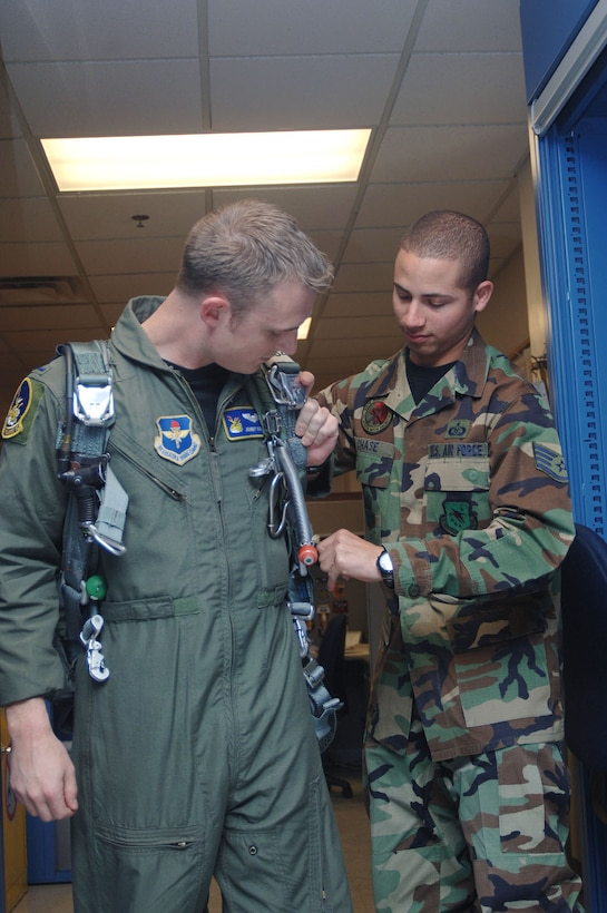 Staff Sgt. James Chase, 50th Flying Training Squadron Life Support, helps 1st Lt. Johnny Koegel, 50th FTS, tighten the straps on his parachute before going out to a flight.