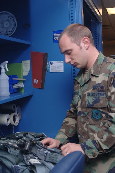 Senior Airman Shannon Smith, 50th Flying Training Squadron Life Support, inspects equipment as part of his daily routine.