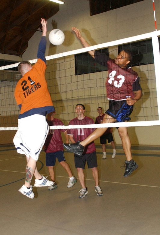 No. 43 Laverne Jackson, a member of the 17th Mission Support Group Junkyard Doggs voleyball team, spikes over No. 21, Kevin Griffin of the 17th Training Support Squadron Tigers.  (U.S. Air Force photo by Airman 1st Class Kamaile Chan)