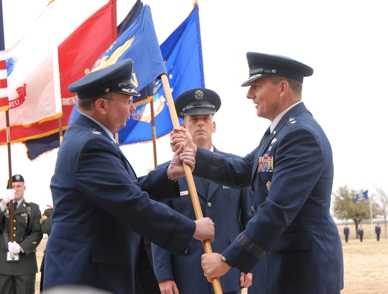 From left to right:  Col. Richard Ayres officially takes command of the 17th Training Wing guidon from Maj. Gen. Michael Gould, 2nd Air Force commander, while Chief Master Sgt. Paul Moreau (center), 17 TRW command chief, stands at attention during a change of command ceremony Mar. 9 at the base parade grounds.  (U.S. Air Force photo by Staff Sgt. Angela Malek)