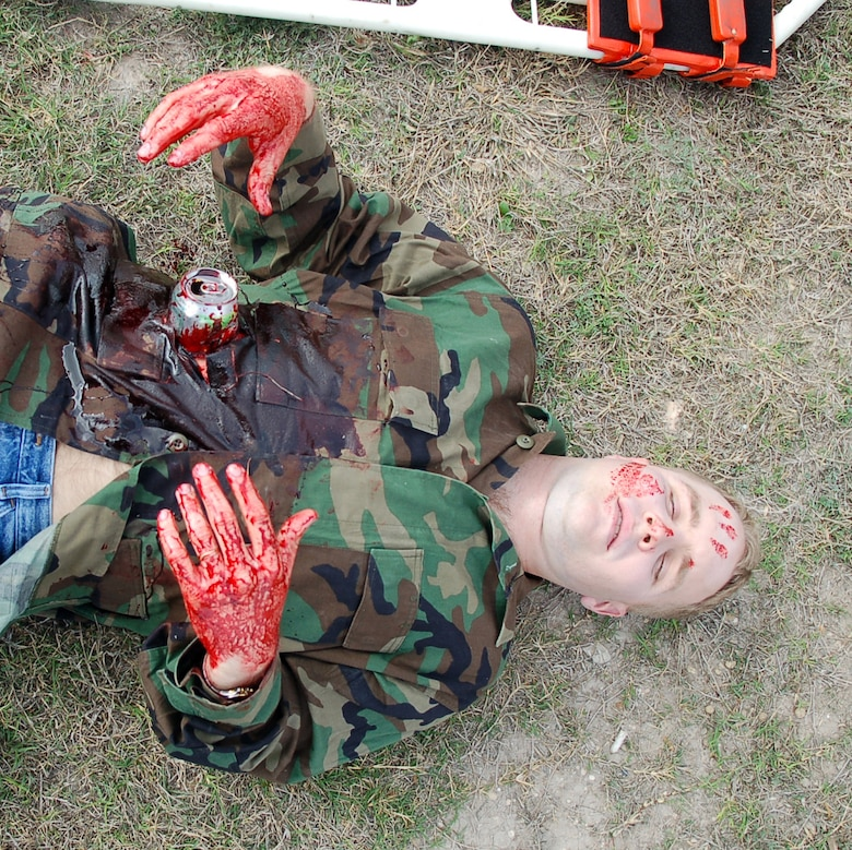 """LAUGHLIN AIR FORCE BASE, Texas -- Sticky with simulated blood, a soda can """"protruding"""" from his belly, 2nd Lt. Todd Mickel lays helplessly awaiting medical attention during an exercise involving a simulated tornado touch down near Outdoor Recreation.  (U.S. Air Force photo by Staff Sgt. Austin M. May)"""