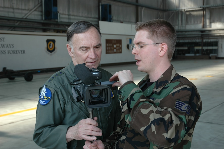 SPANGDAHLEM AIR BASE, Germany -- Gen. Tom Hobbins, U.S. Air Forces in Europe commander, talks with Staff Sgt. Brandon Hoyt, American Forces Network, Detachment 9, about a commercial being filmed for AFN here March 15.
