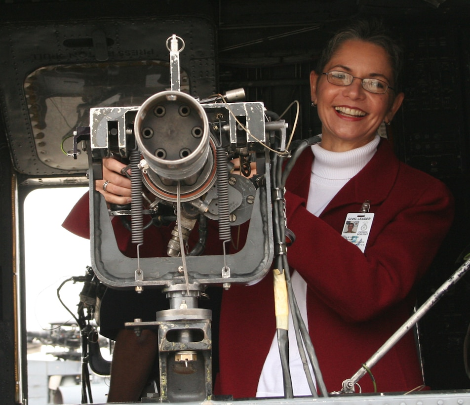 Carla Reinlie, 1st SOW honorary commander from Okaloosa-Walton College, shows her skill at handling the gun on an MH-53 PAVE LOW during a tour. (Courtesy photo)