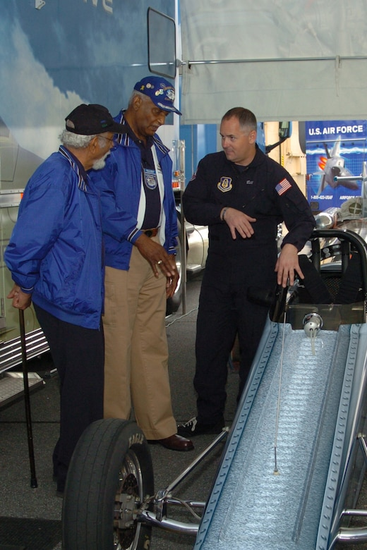 Air Force Reserve Jet Car driver, retired Master Sgt. Bill Braack discusses performance of the jet car with  Atlanta Chapter Tuskegee Airmen, retired Master Sgt. Val Archer and retired Chief Master Sgt. Donald Summerlin during JROTC Week at Dobbins ARB.