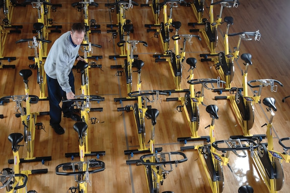 MCCHORD AIR FORCE BASE, Wash. -- Staff Sgt. Ronald West prepares for the fitness improvement class by straighting a row of spin bikes  March 9, 2007 at the fitness center annex. Sergeant West is a certified personal trainer assigned to the 62nd Services Squadron. (U.S. Air Force photo/Abner Guzman)