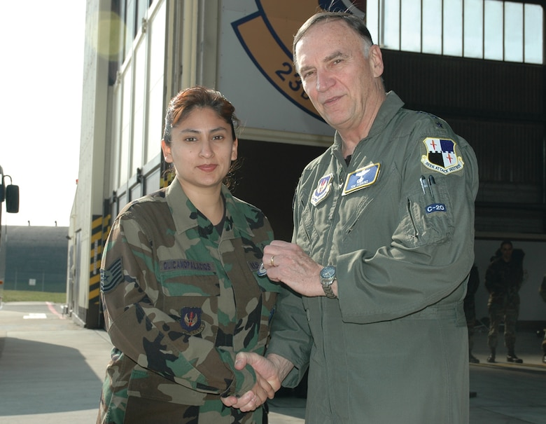 SPANGDAHLEM AIR BASE, Germany -- Gen. Tom Hobbins, U.S. Air Forces in Europe commander, coins Tech. Sgt. Margie Quicanopalacios, 52nd Fighter Wing, while at Spangdahlem Air Base to shoot an American Forces Network commercial here March 15.