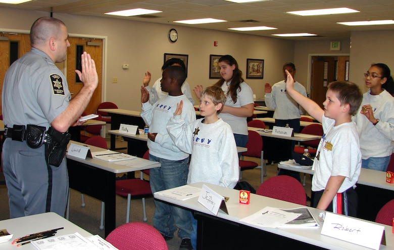 Drug Education for Youth program participants swear in as junior deputy officers during the phase II DEFY March workshop. Guest speaker, Deputy John Droney from the Charleston County Sheriff?s Office, instructed the class on gang resistance and dealing with bullies. (U.S. Air Force photo by Tech. Sgt. Nina Murphy)