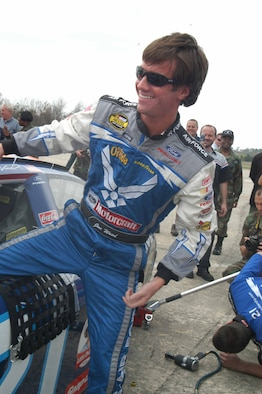 Jon Wood, driver, climbs out of the #21 Air Force car,Thursday March 15 during the pit crew competition. U. S. Air Force photo by Sue Sapp