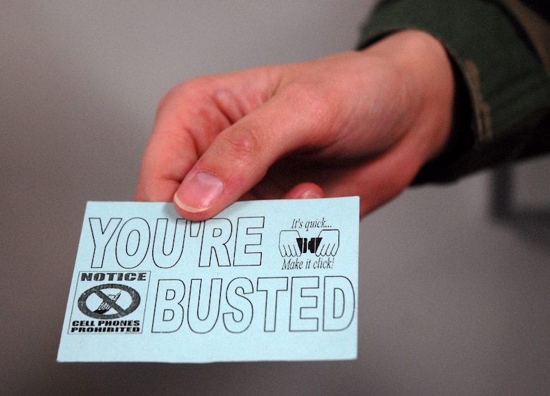 "The 437th Airlift Wing Safety Office will be handing out ""You're Busted"" cards to Arimen found not wearing a seat belt or while driving while talking on a cell phone without a hands-free device. (U.S. Air Force photo/Senior Airman Sam Hymas)"