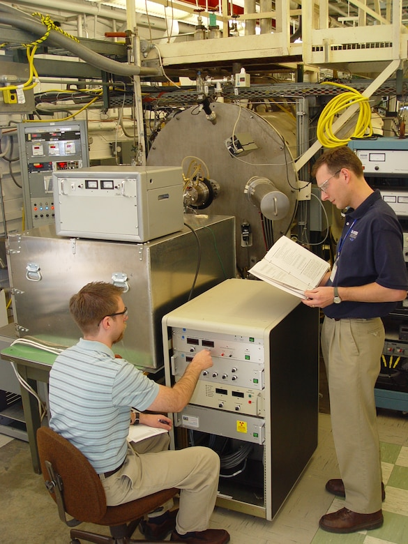 (From left) Dustin Crider, a physicist in ATA's Technology and Analysis Branch, and ATA Space Chamber Research Lab Project Manager John Prebola adjust the Characterization of Combined Orbital Surface Effects (CCOSE) chamber's electron source output to match the low earth orbit environment in preparation for a checkout of the newly configured CCOSE chamber. (Photo by Philip Lorenz III)