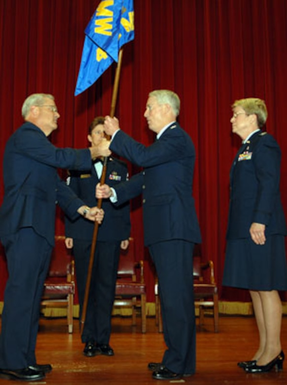 Brig. Gen. James L. Melin, 452d Air Mobiltiy Wing commander, left, hands the medical group guidon to the new 452d Medical Group commander Col. Raymond M. Butler, center, while former commander Col Janice McKibban looks on.  (U.S. Air Force photo by 4th Combat Camera Squadron)