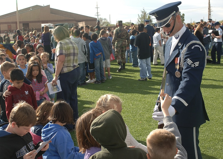 A member of the Air Force Honor Guard Drill Team talks with Holloman children about being on the team and signs autographs. The Drill Team mission is to recruit, retain and inspire for Air Force Recruiting Service. (U.S. Air Force photo by Airman 1st Class John Strong)