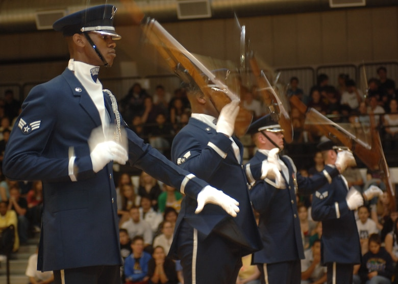 The 16 members of the Air Force Honor Guard Drill Team spin the M-1 rifle with fixed bayonet in a perfect domino effect during a performance at Alamogordo High School. The Drill Team mission is to recruit, retain and inspire for Air Force Recruiting Service. (U.S. Air Force photo by Airman 1st Class John Strong)