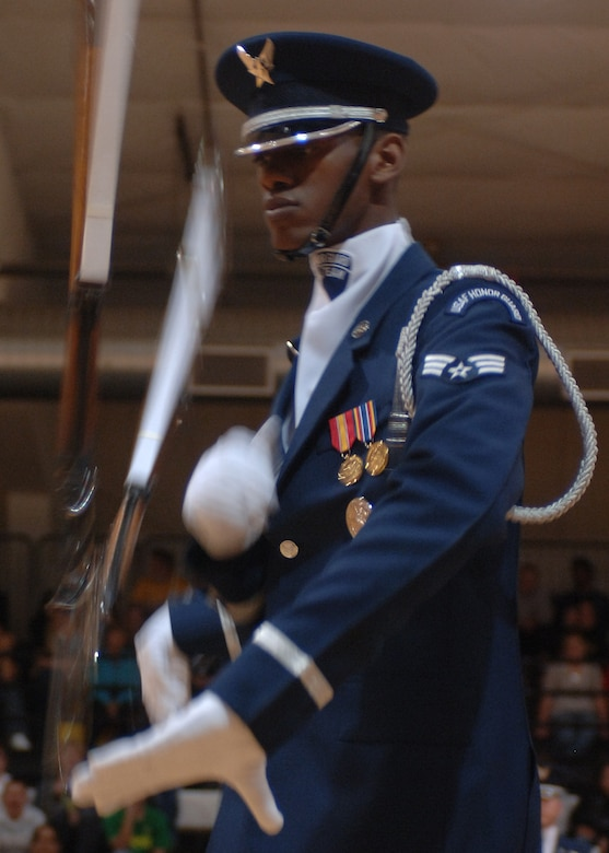 A member of the Air Force Honor Guard Drill Team spins the M-1 rifle with precision and skill during a performance at Alamogordo High School. The Drill Team mission is to recruit, retain and inspire for Air Force Recruiting Service. (U.S. Air Force photo by Airman 1st Class John Strong)