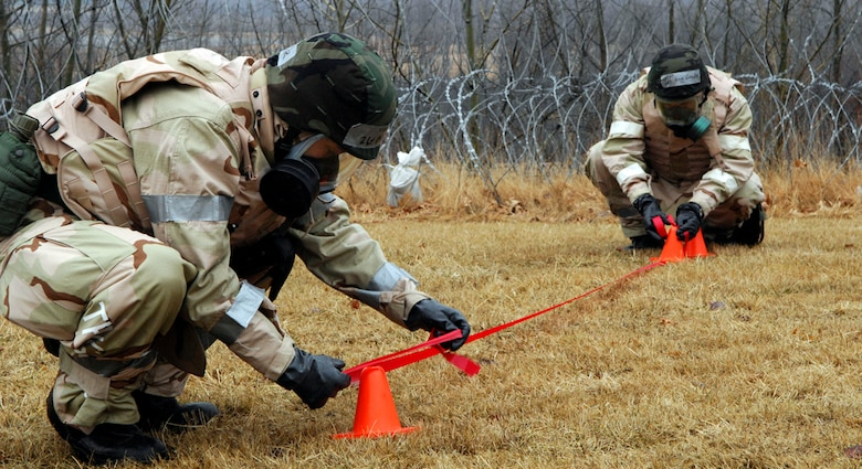 Airmen mark off an area near a simulated Unexploded Ordnance during the March Base Readiness Exercise March 16. The exercise was held in preparation for the upcoming June Operational Readiness Inspection. (U.S. Air Force Photo by Walter Santos)