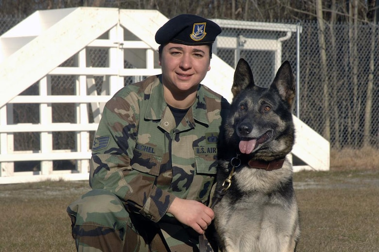 Staff Sergeant Jeanette Reichel, 66th Security Forces Squadron, poses with her Military Working Dog, Petya, a 6-year old German Sheppard, tattoo F-028. Sergeant Reichel entered the Hanscom history books on March 21 as the first female dog handler here in the past two decades after successfully completing her handler certification. (U.S. Air Force Photo by Linda LaBonte Britt)
