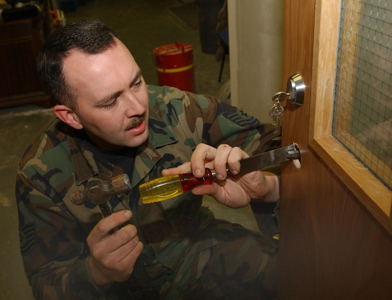 Tech. Sgt. Phillip Young, a  locksmith with the 100th Civil Engineer Squadron, prepares to install a door handle in Building 707, March 14, 2007. (U.S. Air Force photo by Airman Brad Smith)
