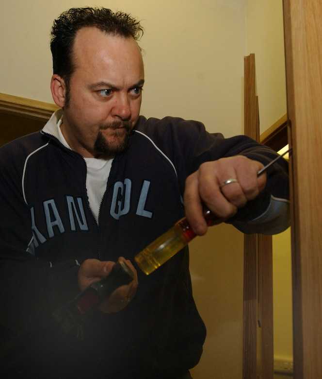 John Cooper, 100th Civil Engineer Squadron Lock Shop, and a Ministry of Defence civilian, chisels out part of the door edge, before installing an Assa mortice lock on a conference room door March 14, 2007, in the 95th Reconnaissance Squadron, in Building 707. The lock smiths often have to make minor adjustments to doors and fittings to ensure locks fit properly and are secure. (U.S. Air Force photo by Airman Brad Smith)