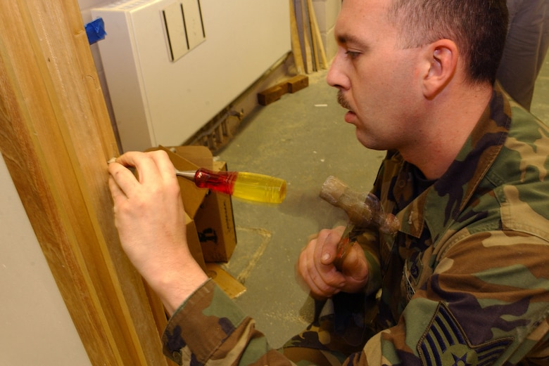 Tech. Sgt. Phillip Young, a locksmith from the 100th Civil Engineer Squadron, hammers a strike plate into a door wall March 14, 2007, at the 95th Reconnaissance Squadron, in building 707. (U.S. Air Force photo by Airman Brad Smith)