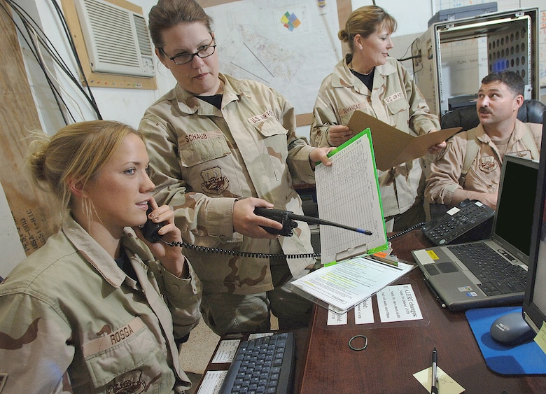 BALAD AIR BASE, Iraq -- (from left) Senior Airman Nicole Rosga, Tech. Sgt. Kerry Schaub, Senior Master Sgt. Marcia Dumancas and Lt. Col. Guy Schaumburg, 332nd Expeditionary Fighter Squadron operations, discuss the day's flying schedule. Of the more than 250 Duluth Guardsmen deployed here to the 332nd Air Expeditionary Wing's 'Tuskegee Airmen,' 41 are related. Sergeant Dumancas is deployed here with her daughter, Airman 1st Class Leilani Dumancas, and Sergeant Schaub with her sister, Lt. Col. Penny Dieryck. (U.S. Air Force photo/Airman 1st Class Nathan Doza)