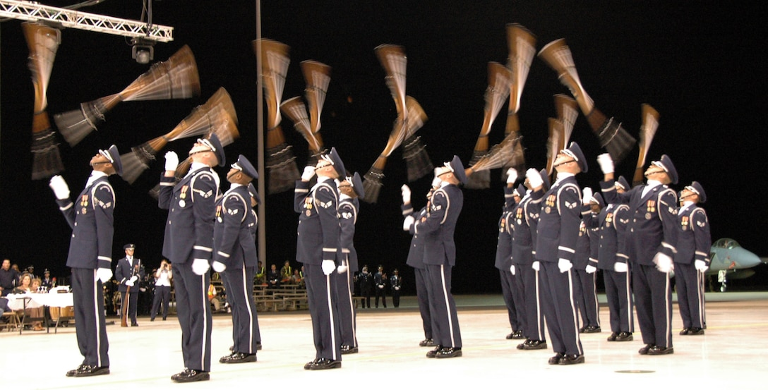 Members of the U.S. Air Force Honor Guard drill team show off their skill with behind the back tosses. U.S. Air Force photo by Sue Sapp