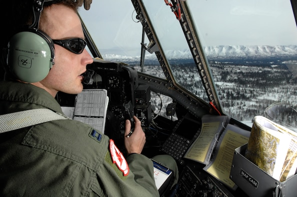 OVER ALASKA -- Capt. Ryan Hendrickson looks out over the vast Alaska wilderness during the final C-130 flight for the 517th Airlift Squadron March 23. After 43 years of continuous service in Alaska, the flight marked the end of the C-130 era at the 517th AS and will see the C-17 taking over the mission soon. The flight was also significant for other reasons to Captain Hendrickson, who proposed to his girlfriend, Charui, shortly after landing. (U.S. Air Force photo by Tech. Sgt. Keith Brown)