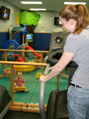 Shara Cooley, tries out one of the treadmills at the Family Fitness Center while watching her daughter, Emily play in the children's area.