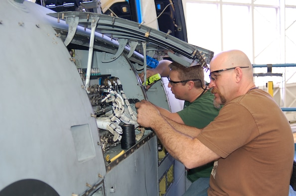 Dennis Miller (right) and Chris Ward inspect the wiring in A-10 panels before sending the aircraft to the fuel dock. Photo by Bill Orndorff