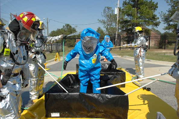 """MOODY AIR FORCE BASE, Ga. -- Members of the 23rd Civil Engineer Squadron, Moody Air Force Base, Ga., wear level A chemical suits as they decontaminate another Team Moody member after fixing a chlorine gas cylinder leak during the Operational Readiness Exercise """"Commando Angel"""" March 19. The exercise, held March 19-23, tests the base's ability to rapidly deploy and operate in a simulated forward operating location.(U.S. Air Force photo by Airman 1st Class Gina Chiaverotti)"""
