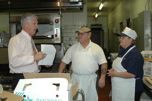 Garry Shaffer, Dakota's manager, speaks with Ms. Nancy Powers and Mr. Edward Newigham, Dakota's cooks, as they prepare to serve lunch.