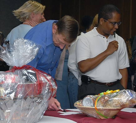 Col. Lansen Conley, vice commander of the 82nd Training Wing, and Lt. Col. Linnes Chester Jr., deputy commander of the 882nd Training Group, ponder which baskets to bid on during the inaugural Air Force Assistance Fund Basket Auction March 20 at the Sheppard Club. The auction raised more than $5,700 for the AFAF Campaign. (U.S. Air Force photo/Mike Litteken)