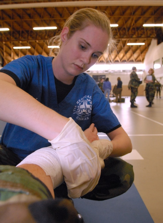Staff Sgt. April Miller wraps the arm of a victim during the natural disaster exercise March 13 at Goodfellow Air Force Base. (U.S. Air Force photo by Tech. Sgt. Randy Mallard)