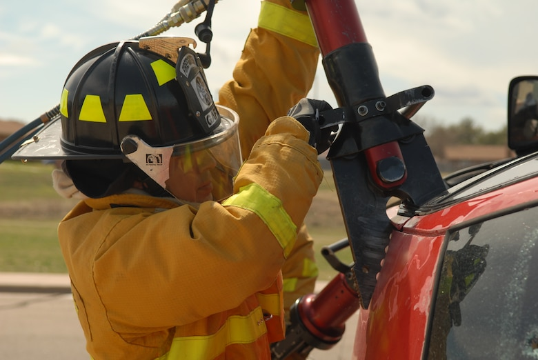 A firefighter attempts to rip open the ceiling of a vehicle used during a natural disaster exercise on Goodfellow Air Force Base March 13. (U.S. Air Force photo by Tech. Sgt. Randy Mallard)