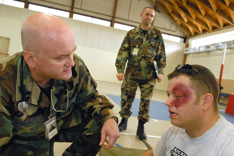 Capt. Paul Schroth (left) assesses the injuries suffered by an exercise car accident victim while and Exercise Evaluation Team member (center) looks on during a natural disaster exercise on Goodfellow Air Force Base March 13. (U.S. Air Force photo by Tech. Sgt. Randy Mallard)