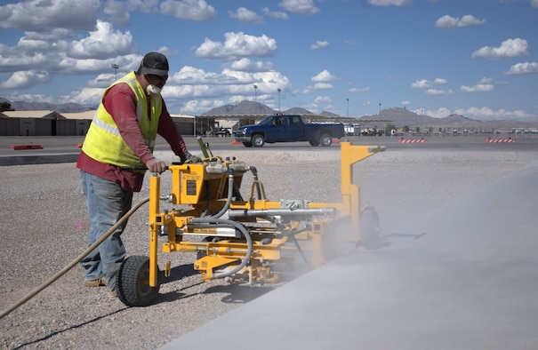 Jose Munez, a construction crew member, utilizes a machine to drill holes into the side of the concrete during work on the ongoing flight line construction project, head by the 99th Civil Engineering Squadron to replace a section of Taxiway Foxtrot.