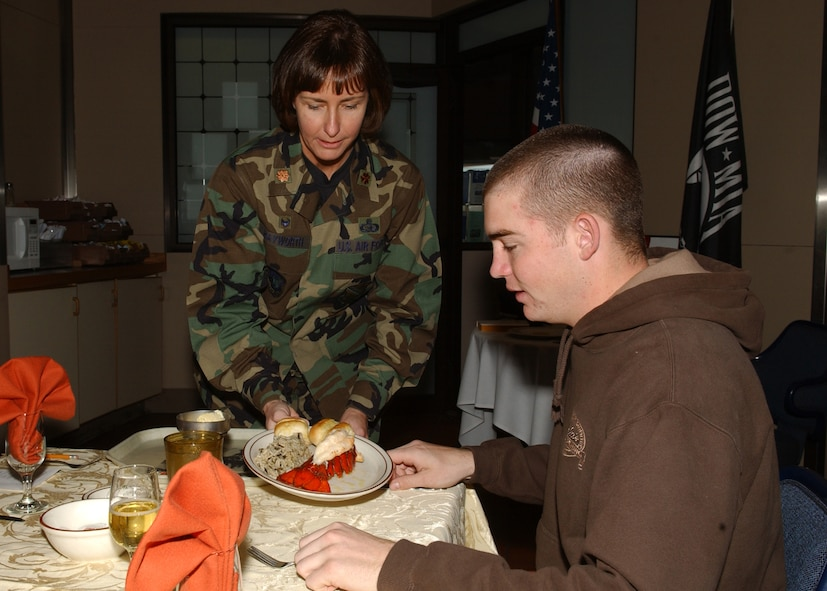 EIELSON AIR FORCE BASE, Alaska -- Maj. Michelle Hayworth, 354th Communications Squadron commander, serves food to Airman Basic Tyler Boschma, 354th Civil Engineering Squadron, during the birthday meal for the February and March babies at Two Seasons Dinning Facility March 22. The dinning facility hosts a birthday meal once every two months to provide Airmen with excellent food and a friendly atmosphere when they are unable to spend it with their families. (U.S. Air Force Photo by Airman 1st Class Jonathan Snyder)