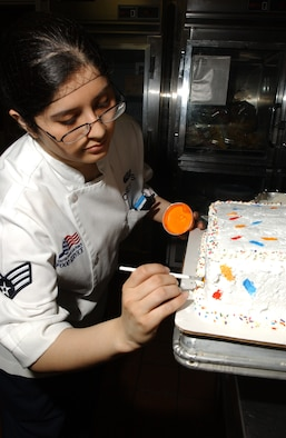 EIELSON AIR FORCE BASE, Alaska -- Senior Airman Cecilia Cuestas, 354th Services Squadron, decorates a two-layered cake for the birthday meal March 22 at the Two Seasons Dinning Facility. The dining facility hosts a birthday meal once every two months for single Airmen unable to spend it with their families. (U.S. Air Force Photo by Airman 1st Class Jonathan Snyder)