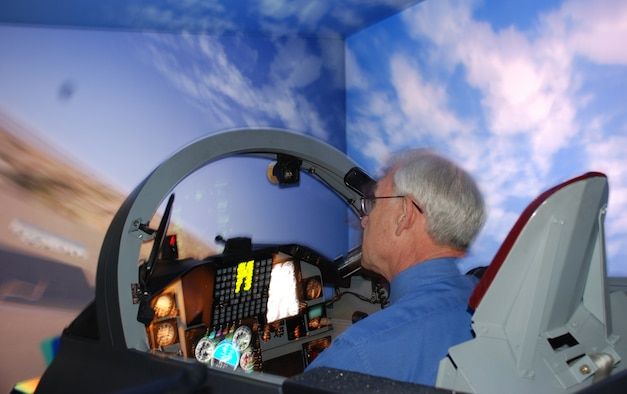 Retired Brig. Gen. Travis Harrell, commander of the Euro-NATO Joint Jet Pilot Training from Dec. 22, 1987, to July 20, 1989, tries out the 80th Flying Training Wing's flight simulator March 26 as part of the ENJJPT 25th Anniversary Celebration. (U.S. Air Force photo/Airman 1st Class Jacob Corbin)