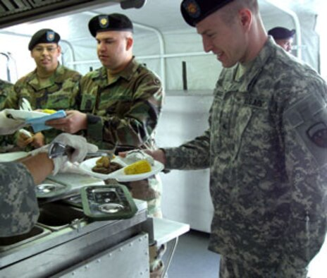 Spc. Raymond Menjiver, left, Spc. Joshua Fouch, and Sgt. Christopher Gimber, right, fill their plates with food from the 304th's Mobile Kitchen.  Soldiers of the 304th Sustainment Brigade at March Air Reserve Base, Calif., were treated to a hot meal on the weekend as part of the debut of the unit's Containerized Kitchen, a trailer that has all of the equipment necessary for meal (U.S. Army photo by Spc. K. Christopher Witt)