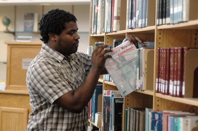 Carles Blackmon, library aide, shelves a book at the Base Library. U.S. Air Force photo by Sue Sapp