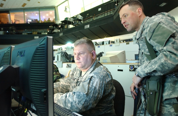 OSAN AIR BASE, Republic of Korea --  Lt. Col. Philip McCutcheon, 3rd Battlefield Coordination Detachment deputy commander, and Sgt. 1st Class Wessley Czap, 3rd BCD operations NCO, analyze incoming data on the computer monitor during RSO&I on Monday. (U.S. Air Force photo by Staff Sgt. Francisco V. Govea II)