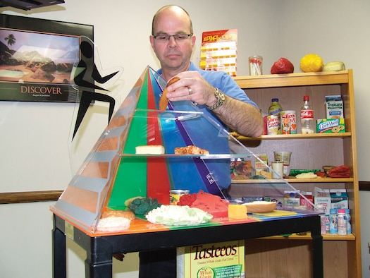 Brent Carney, 62nd Medical Operations Squadron, adjusts a food pyramid display at the Health and Wellness Center Tuesday.  Mr. Carney, the new base dietician, has been a dietician for 18 years. (U.S. Air Force Photo/Tyler Hemstreet)