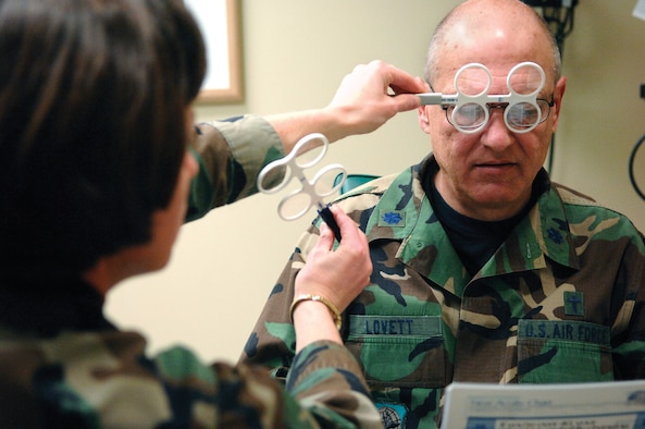 Chaplain (Lt. Col.) Michael Lovett, 62nd Airlift Wing, reads from a near acuity chart during a visit to the Optometry clinic Tuesday March 15, 2007 while Optometrist Major Christine Stabile, 62nd Medical Operations Squadron, uses add lenses to measure for bifocals. (U.S. Air Force photo/Abner Guzman)