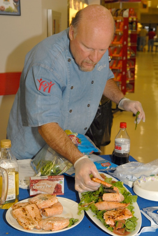 """Chef Henry Weins, of the local TV cooking show """"Let's Eat,"""" adorns a plate of salmon salad while participating in this year's base observance and celebration of National Nutrition Month (March) by providing a cooking demonstration Tuesday at the Goodfellow Commissary (U.S. Air Force photo by Staff Sgt. John Barton)"""