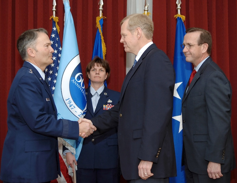 From left, Electronic Systems Center Vice Commander Maj. Gen. Art Rooney shakes Peter Zimmerman's hand during Mr. Zimmerman's instatement as the 554th Electronic Systems Wing's Honorary Wing Commander March 23 at the Minuteman Club. Frank Weber, 554 ELSW director, far left, passed the Air Force's 60th Anniversary flag to Mr. Zimmerman during the ceremony. ESC Command Chief Master Sergeant Lisa Sirois, center back, presented the flag to the base leaders. (US Air Force Photo by Jan Abate)