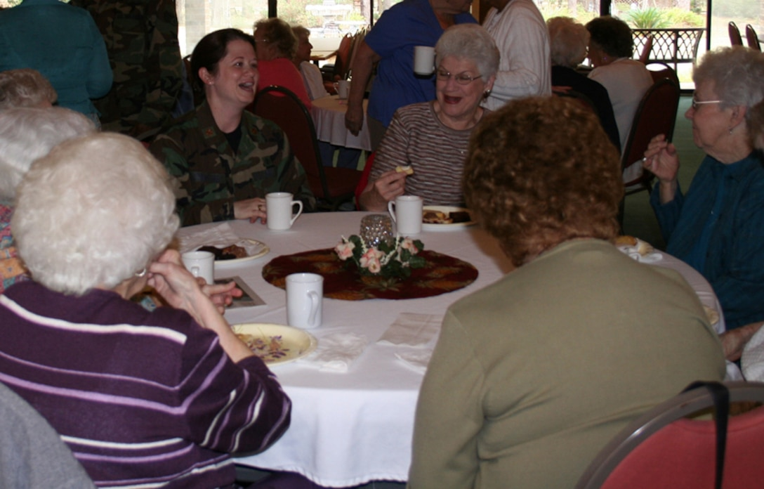 An Airman enjoys the company of Air Force Enlisted Village residents during an afternoon tea March 15. Many women Air Commandos took part in the tea and a workday, assisting the residents with small chores around the village. (U.S. Air Force photo by Jodi Jordan)