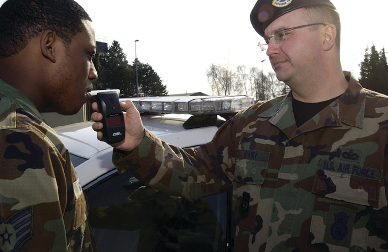 SPANGDAHLEM AIR BASE, GERMANY -- Tech. Sgt. Scott Kuhrt, 52nd Security Forces Squadron, demonstrates the use of a breathalyzer on fellow security forces member Staff Sgt. David Hudson Wednesday. This breathalyzer is carried by members of the  52nd SFS to emergency scenes to detect if an individual is under the influence of alcohol. (Photo by Staff Sgt. Raymond Mills)