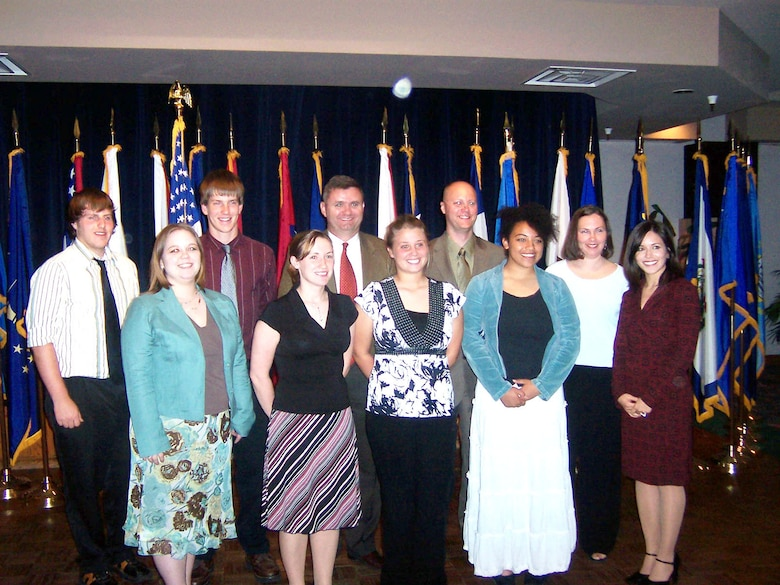 The Officers Spouses and Enlisted Spouses clubs awarded more than $13,000 in scholarships to students April 19. Front row: Angela Minear OSC co-chair, Erin Bailey, Kelsey Ashmore, Iris Grooms and Christine Caldwell. Back row: Eli Godwin, Jayme Nauman, Col. Scott West, 27th Fighter Wing commander, Chief Master Sgt. Allen Millinac, 27th Aircraft Maintenance Squadron, and Bonnie Gillespie. (Courtesy photo)